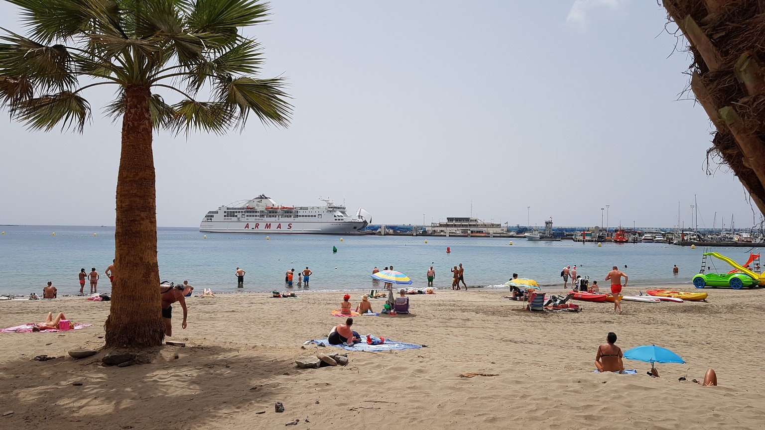 pláž s palmou a lodí