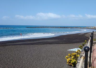 prázdná pláž s tmavým pískem